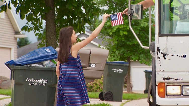 Sydney Dutton gives a flag to her family's garbage man