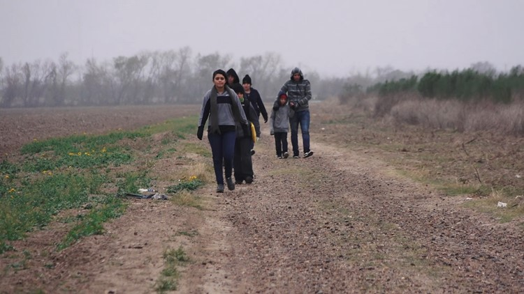 Family unit of Central Americans walk up to Border Patrol after crossing the border.