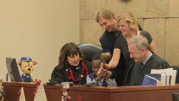 Michael Clark Jr. and his parents making his adoption official
